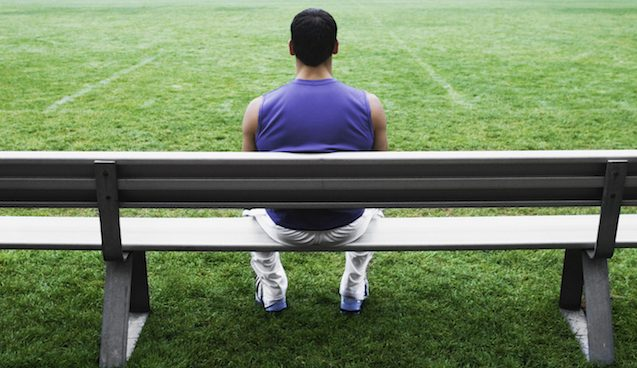 Male athlete sitting on bench